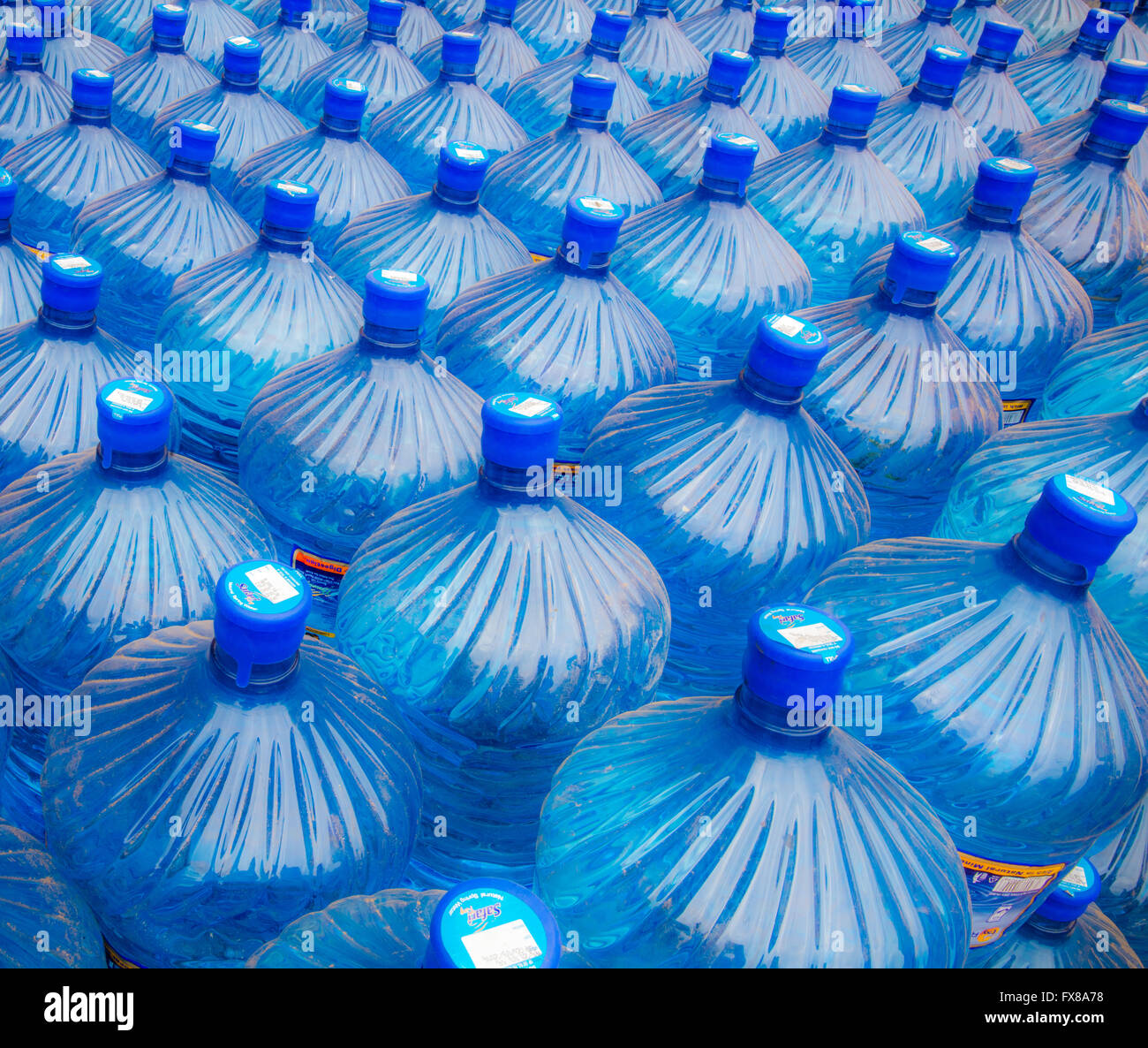 Twenty litre plastic containers of water stacked in rows outside a Kenyan general store in Voi Southern Kenya - Stock Image
