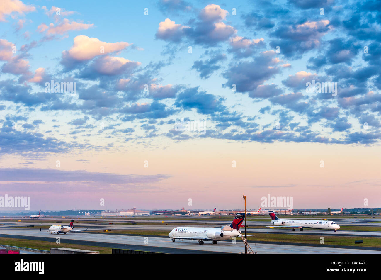 Delta Air Lines jets taxiing under a dramatic sunset sky at Hartsfield-Jackson Atlanta International Airport in - Stock Image