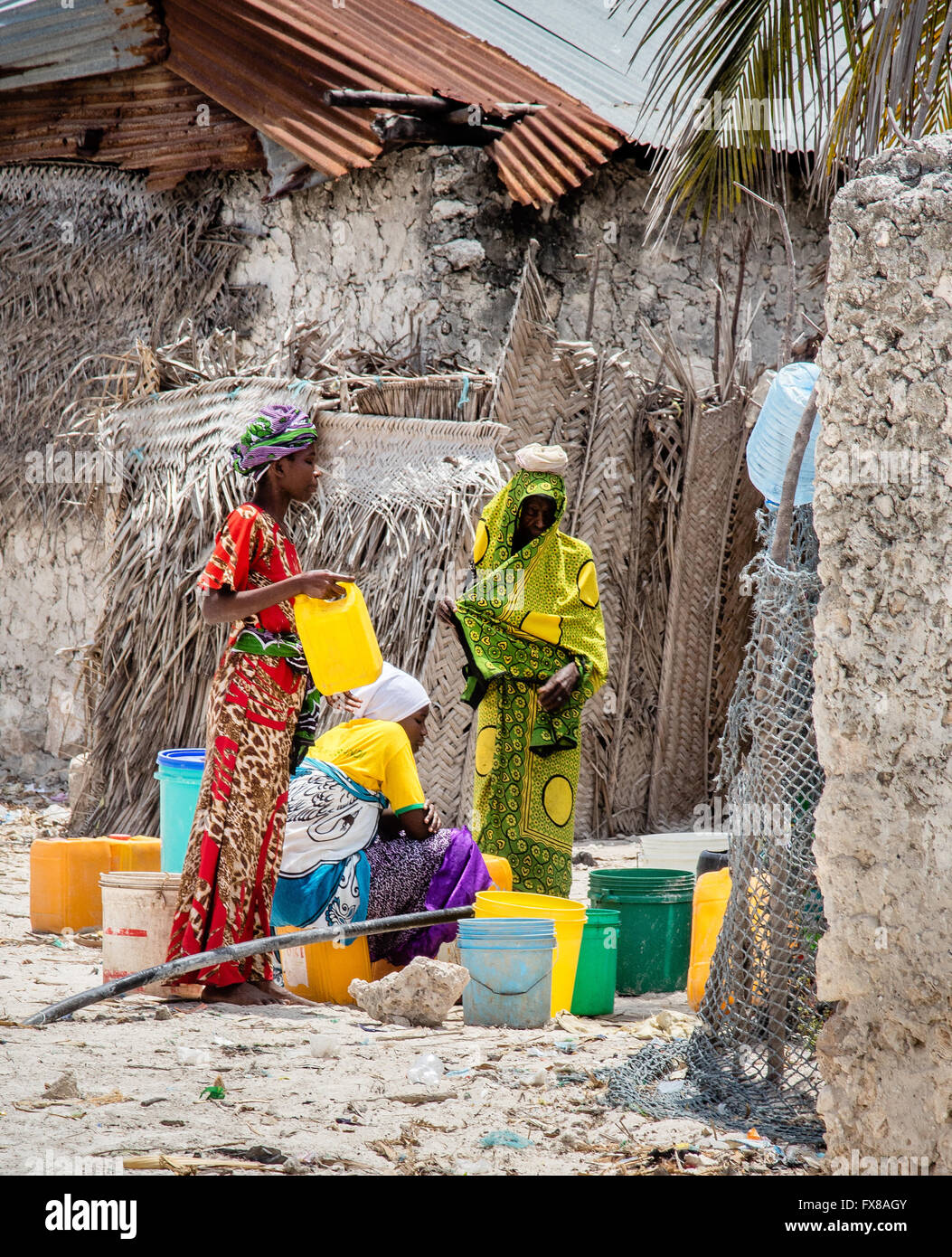Brightly clothed women collect water in plastic containers from a communal tap in a Tanzanian village on Zanzibar - Stock Image