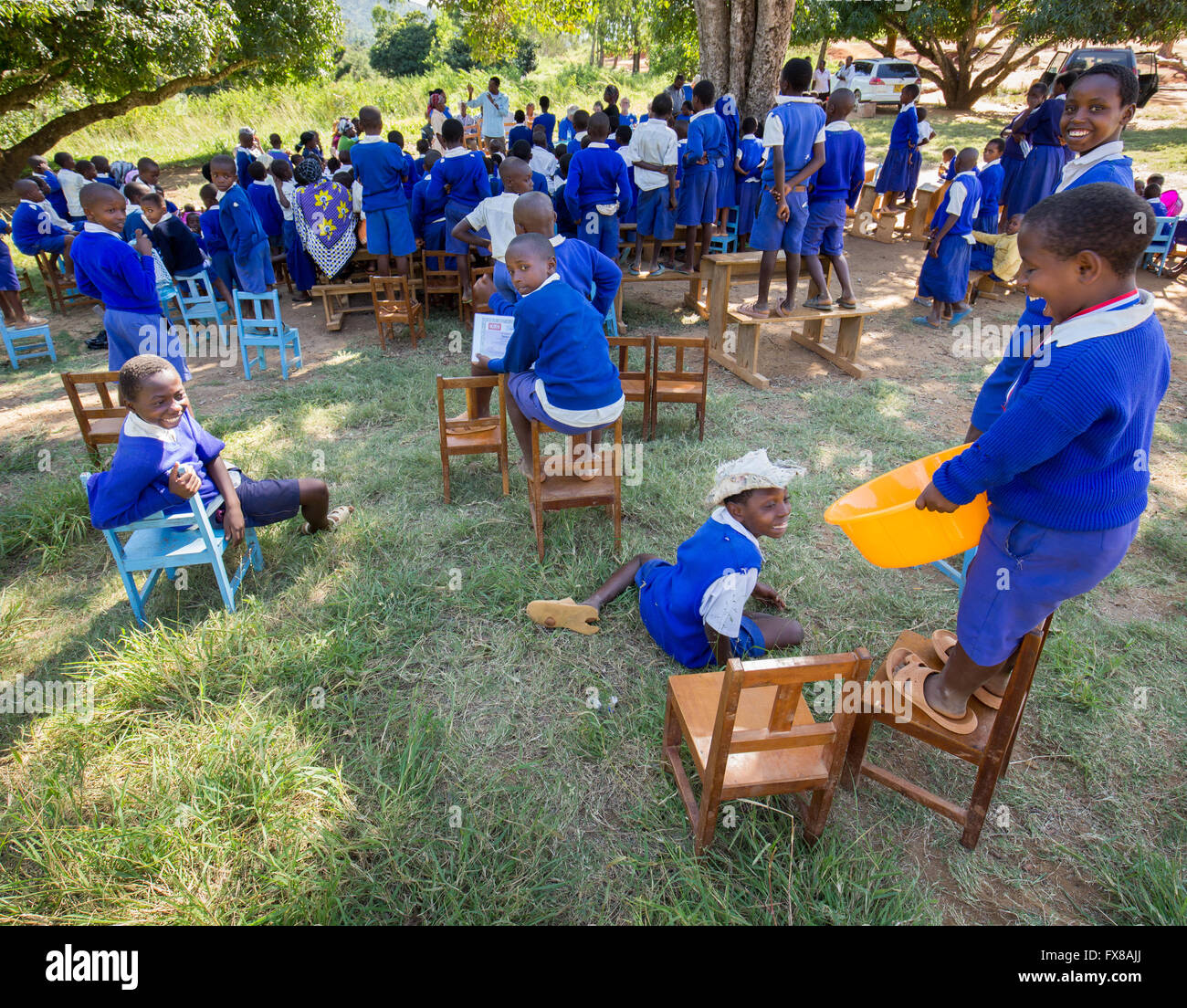 Boys at the back of a school outdoor prize giving ceremony in the Sagalla district of Kenya  laughing and having - Stock Image
