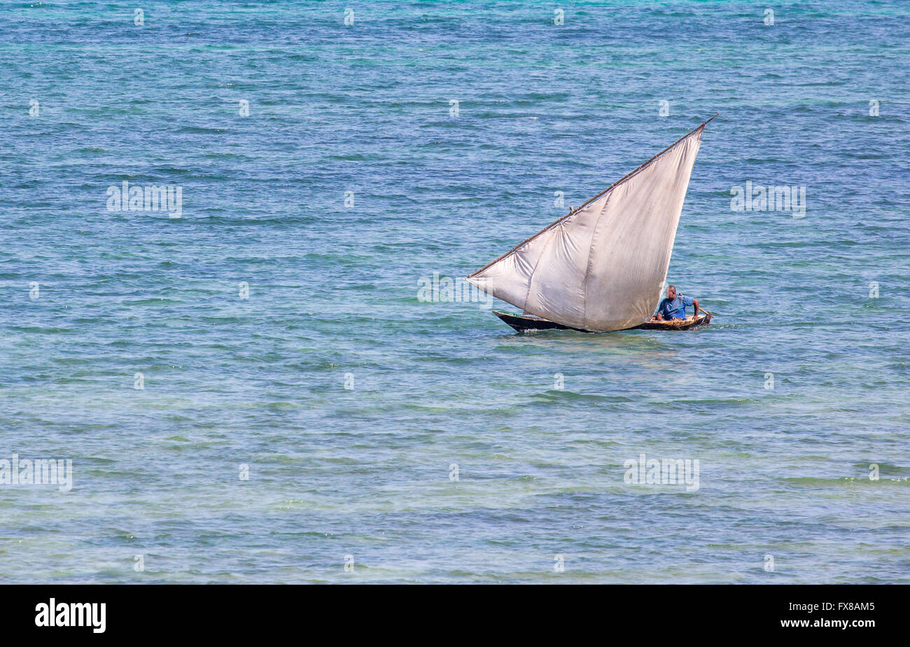 Small dhow sailing on the Indian ocean near the prt of Stone Town on the island of Zanzibar East Africa - Stock Image