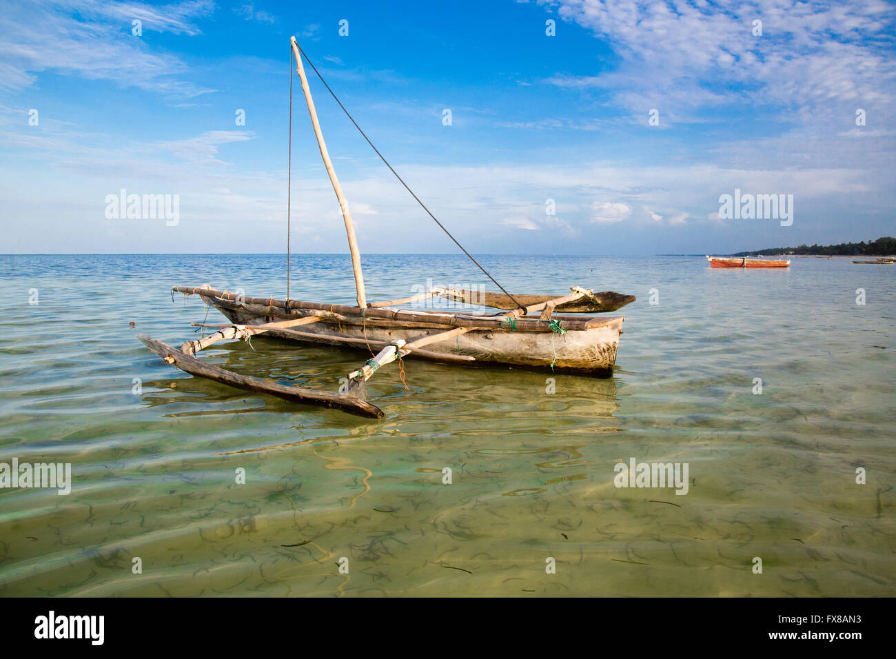 A small dhow moored on a lagoon on the coast of Zanzibar East Africa - Stock Image