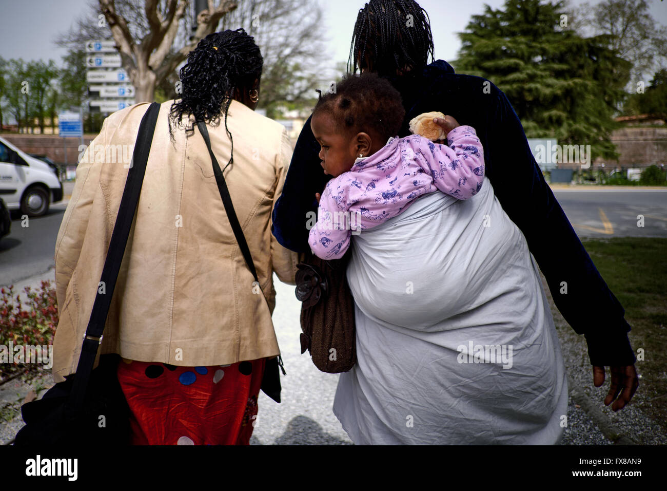 Two black women walking away from camera, one with a young child on her back in a sheet. - Stock Image