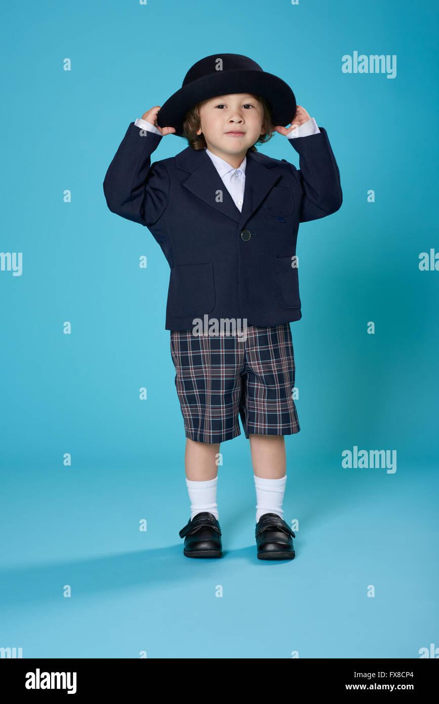 A 3 year old half Japanese, half American boy dressed in a preschool uniform. - Stock Image
