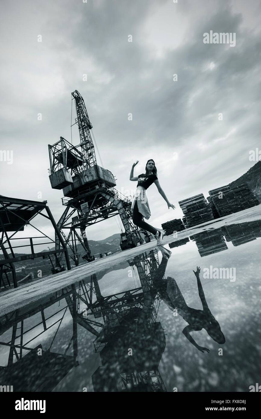 Young woman dance dancing tip-toeing mirror image reflecting pond water crane motion music stand standing full length - Stock Image