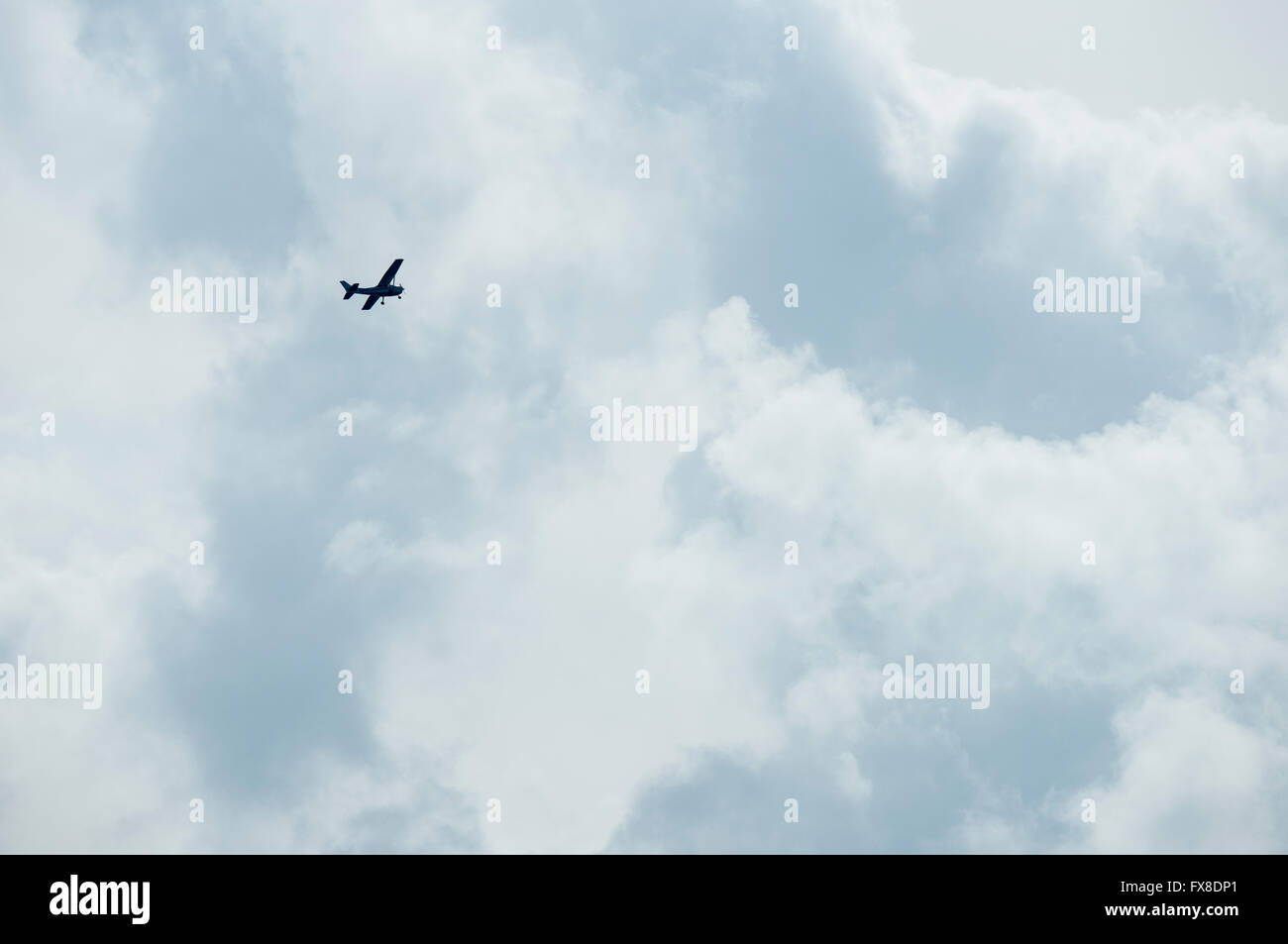 Smal prop plane against cloudy ominus sky - Stock Image