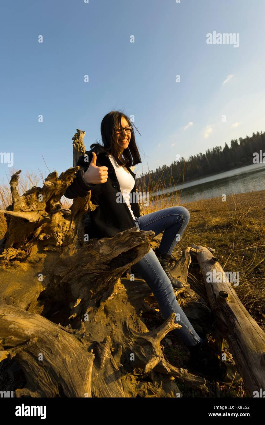 OK affirmative thumb-up teen girl on lake coastline single people stand standing  smile smiling fallen tree Stock Photo