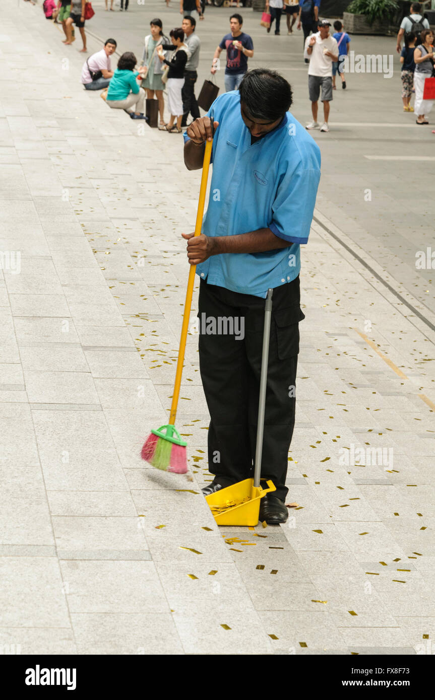 Man sweeping Orchard Road steps, Singapore. - Stock Image
