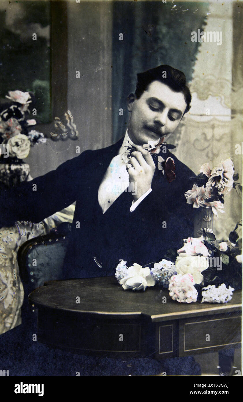 FRANCE I CIRCA 1903: A postgard printed in France shows Man considers flowers sitting at the table, circa 1903 - Stock Image