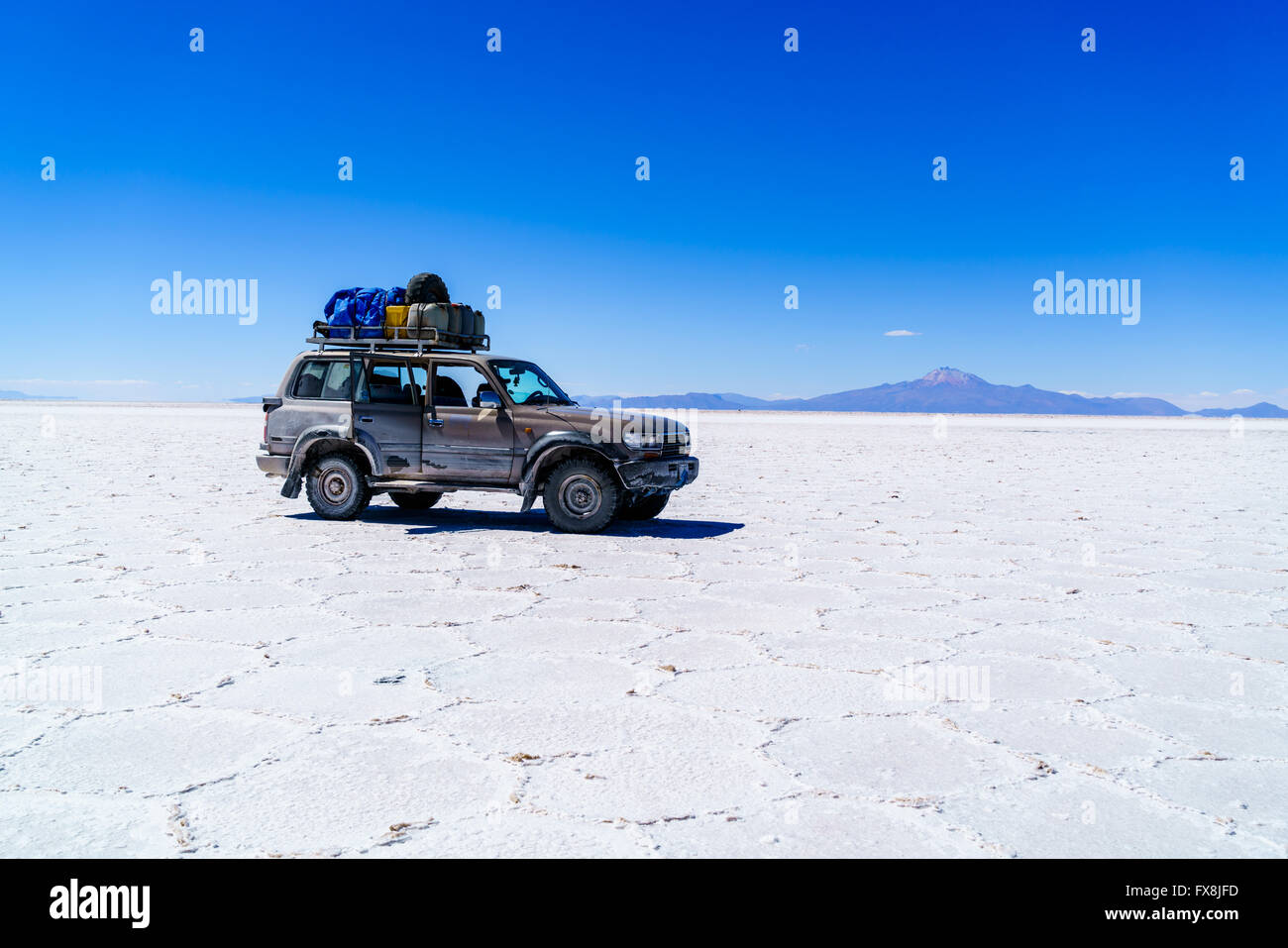 Car in the Salar de Uyuni, the world largest salt flat in Bolivia - Stock Image