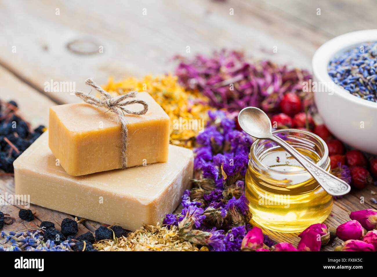 Bars of homemade soaps, honey or oil, heaps of healing herbs and mortar of lavender. Selective focus. - Stock Image