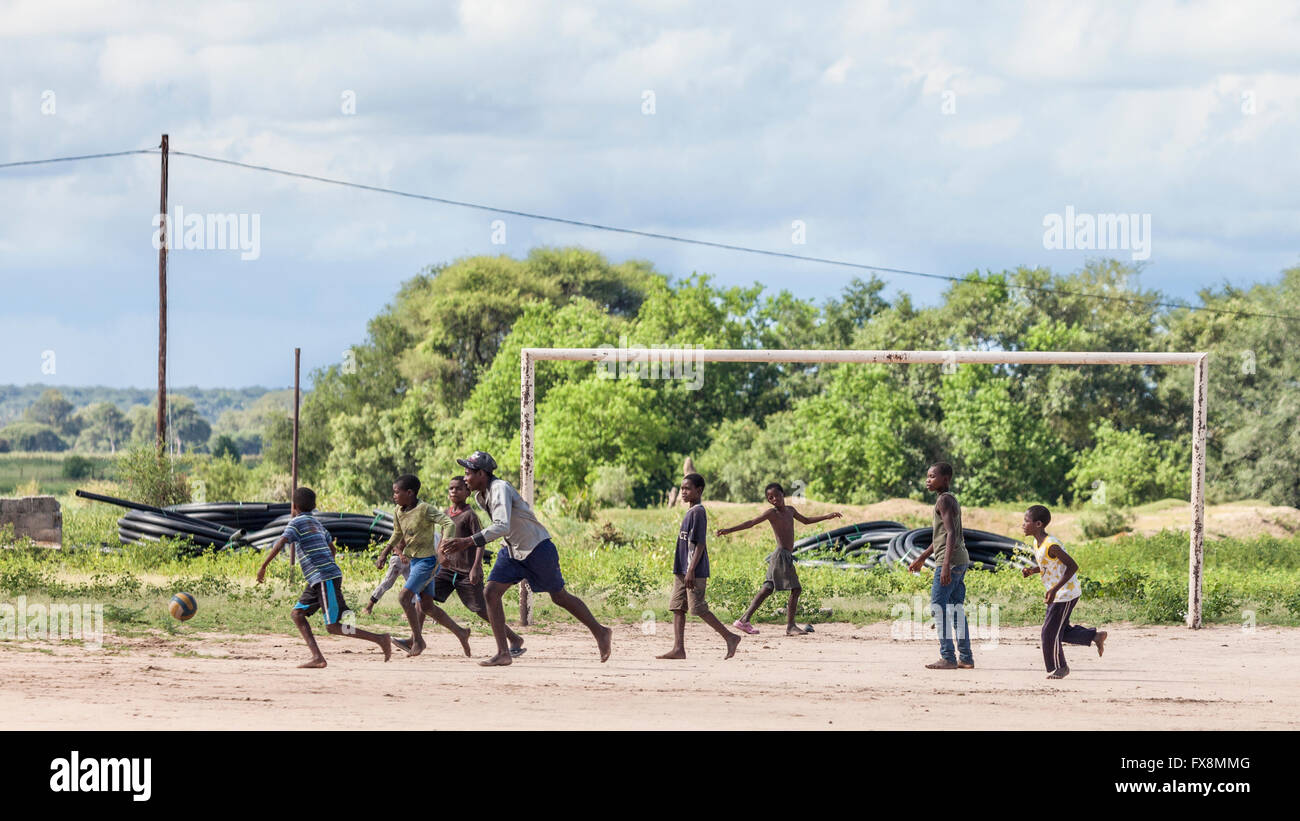 Batswana boys playing football, mostly with bare feet. Near Mohembo West, northern Botswana, southern Africa Stock Photo