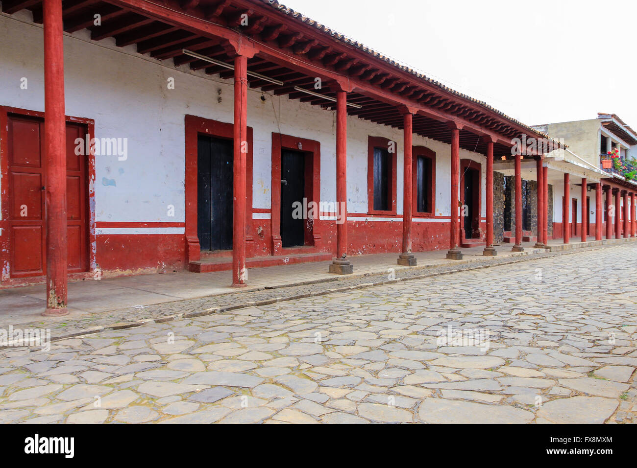 An empty plaza with a row of colorful columns in Tzintzuntzan, Michoacan, Mexico - Stock Image
