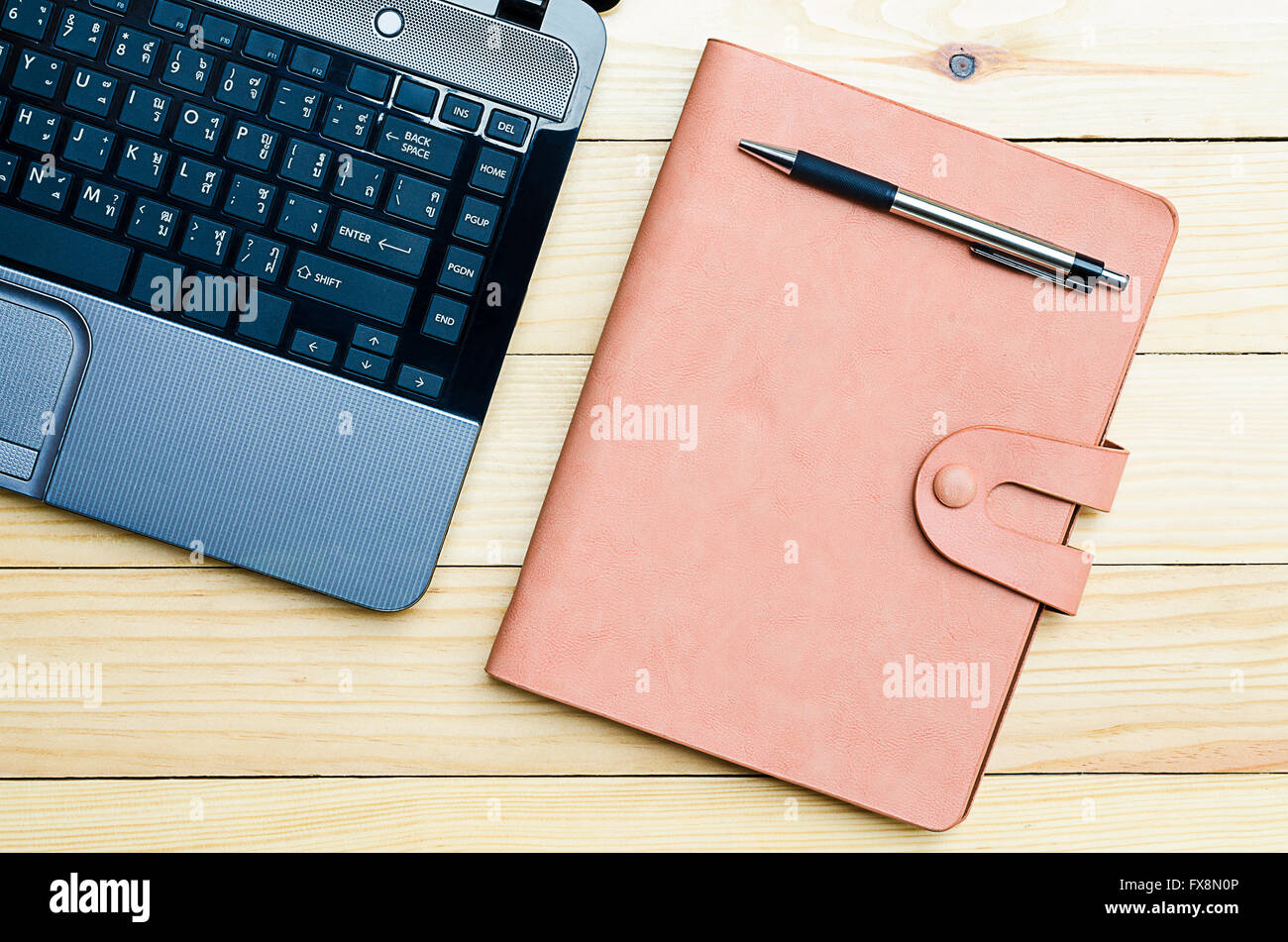 Leather notebook with pen and labtop on office desk.Top view Stock Photo