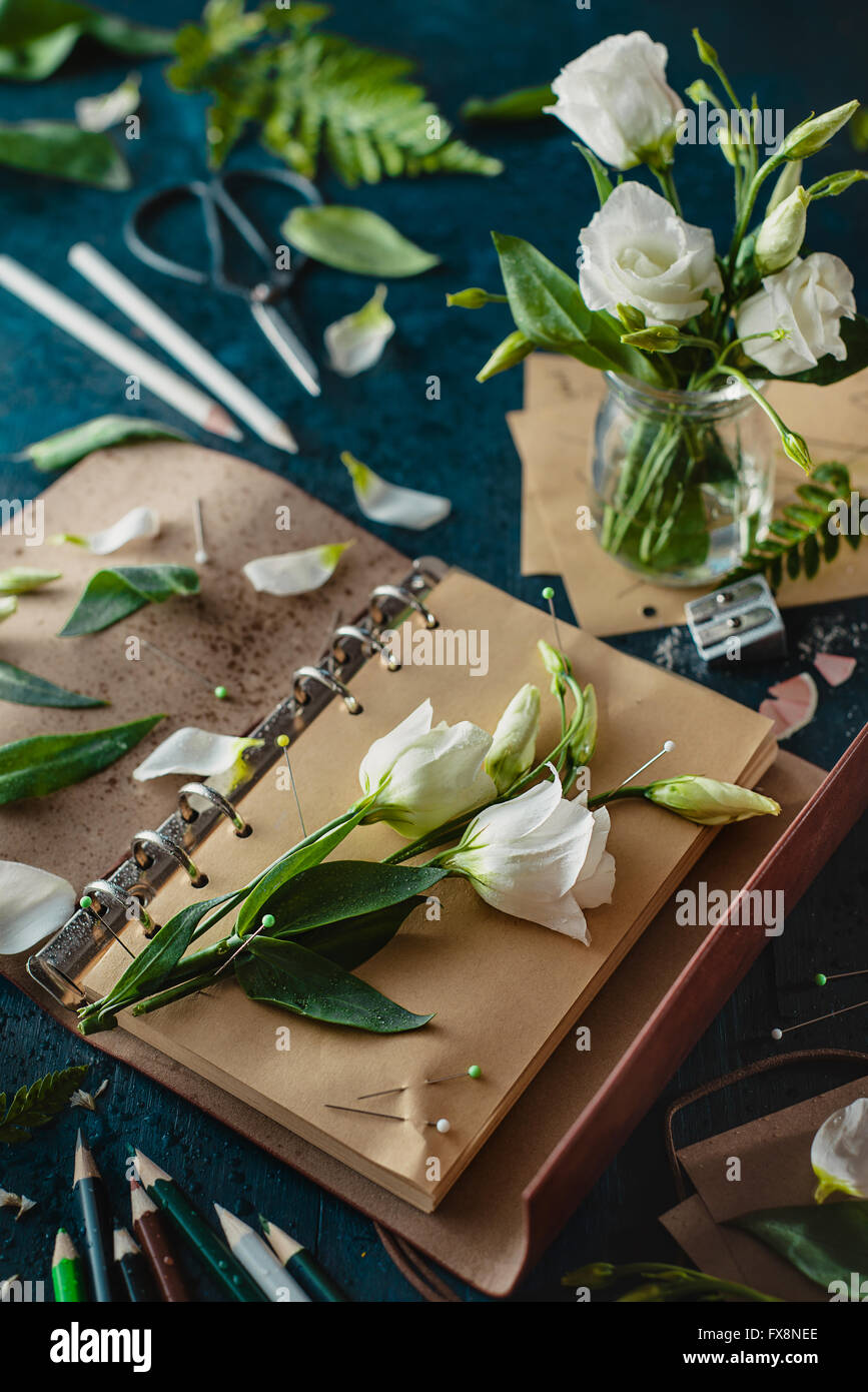 Painting flowers: pins and pencils. Still life with artist's tools and flowers - Stock Image