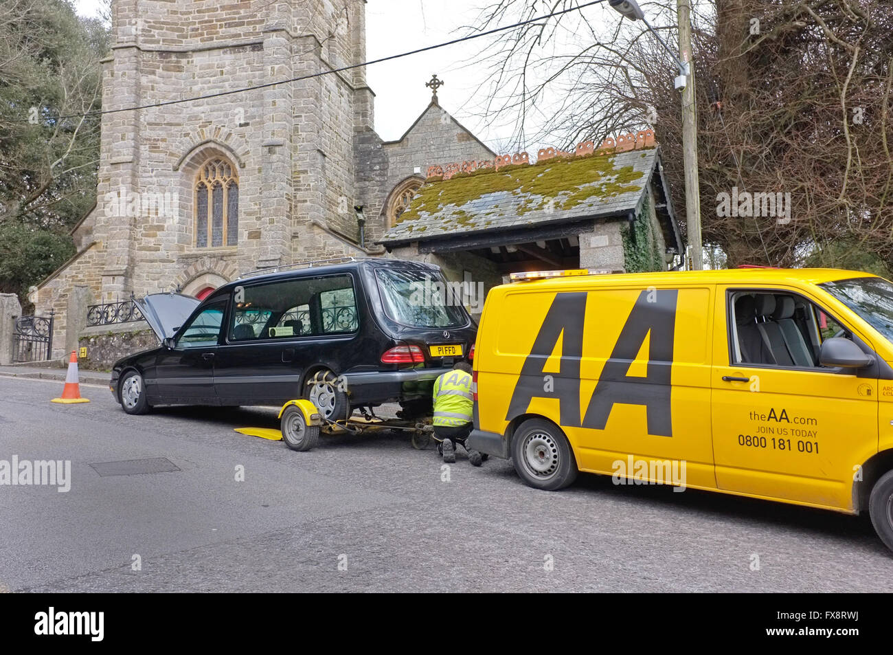 An AA breakdown vehicle preparing to tow away a hearse - Stock Image