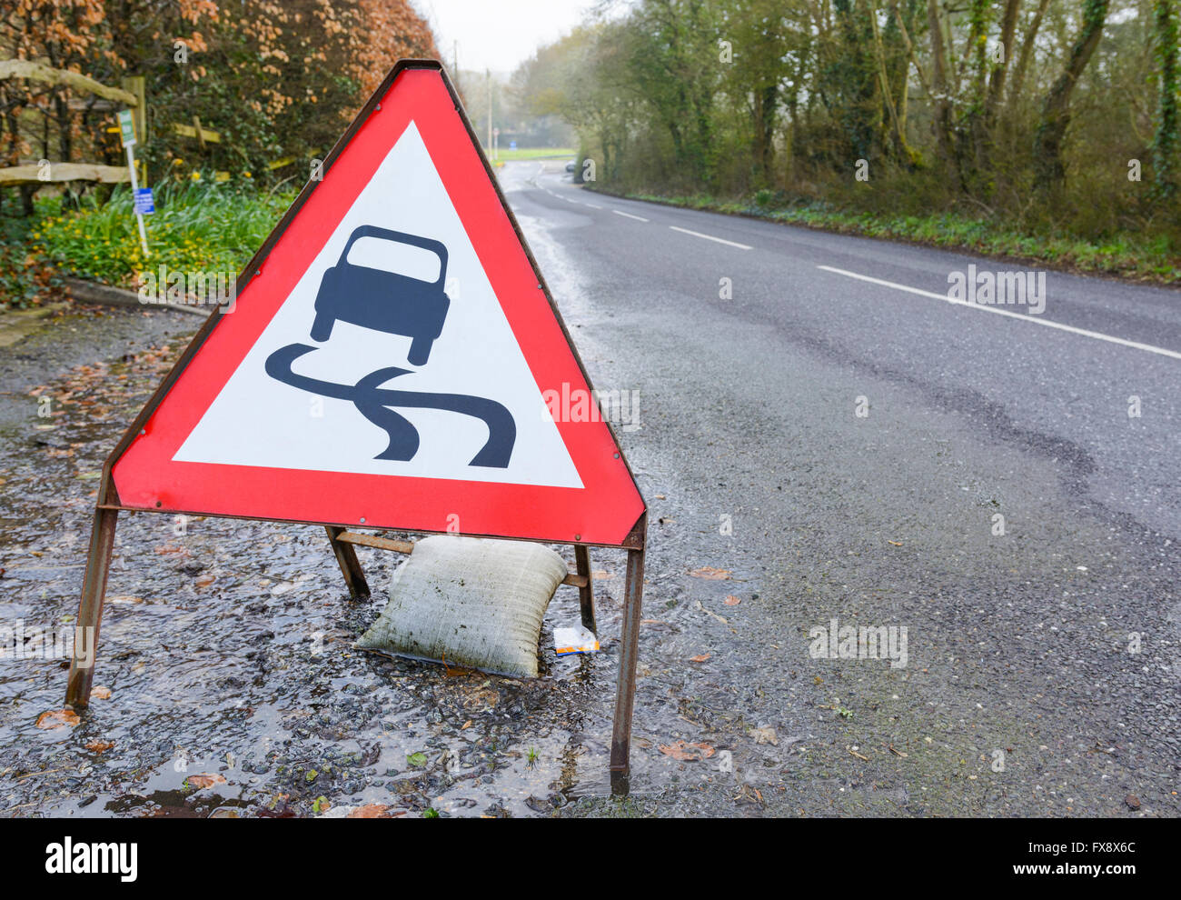 Slippery road triangular warning sign on a flooded road in the UK. Stock Photo