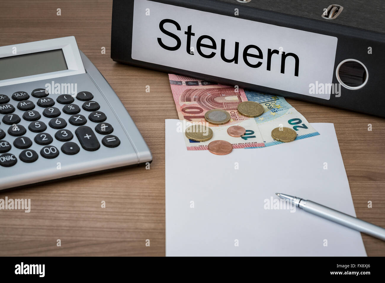 Steuern (German Taxes) written on a binder on a desk with euro money calculator blank sheet and pen Stock Photo
