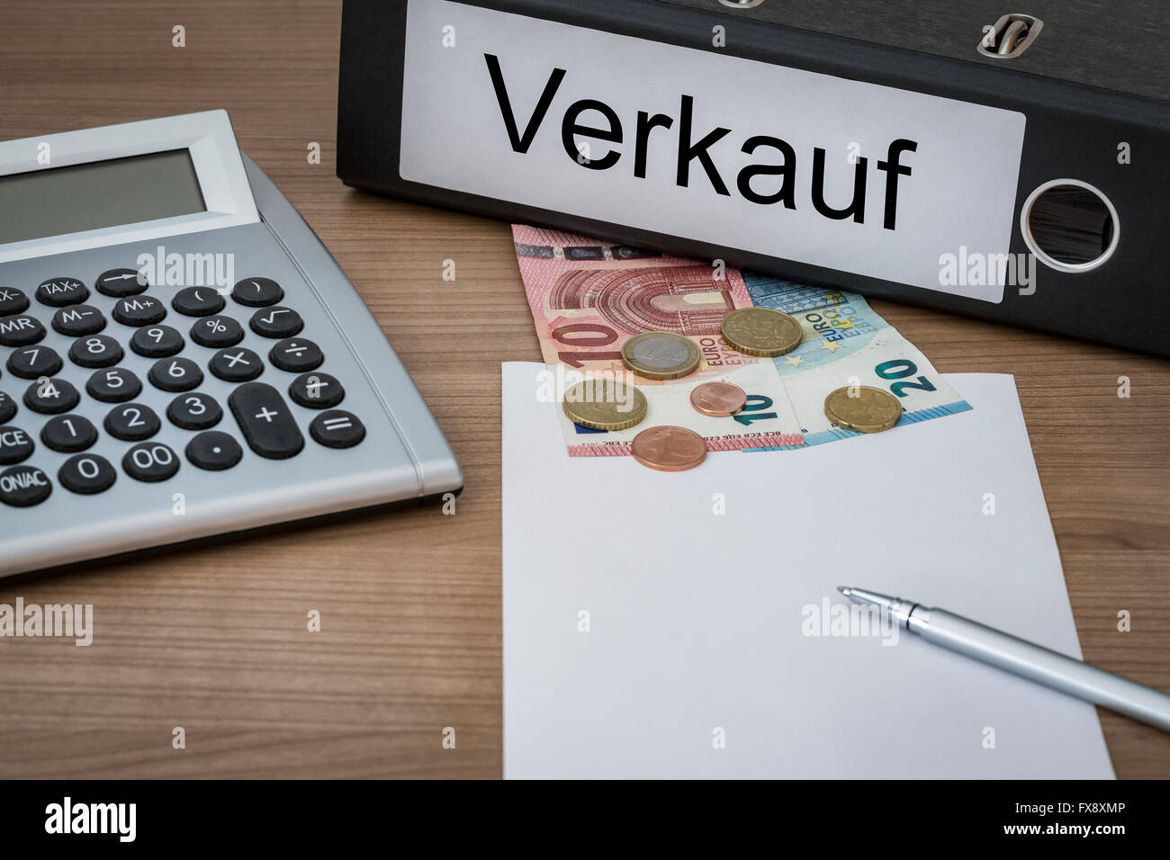 Verkauf (German Sales) written on a binder on a desk with euro money calculator blank sheet and pen - Stock Image
