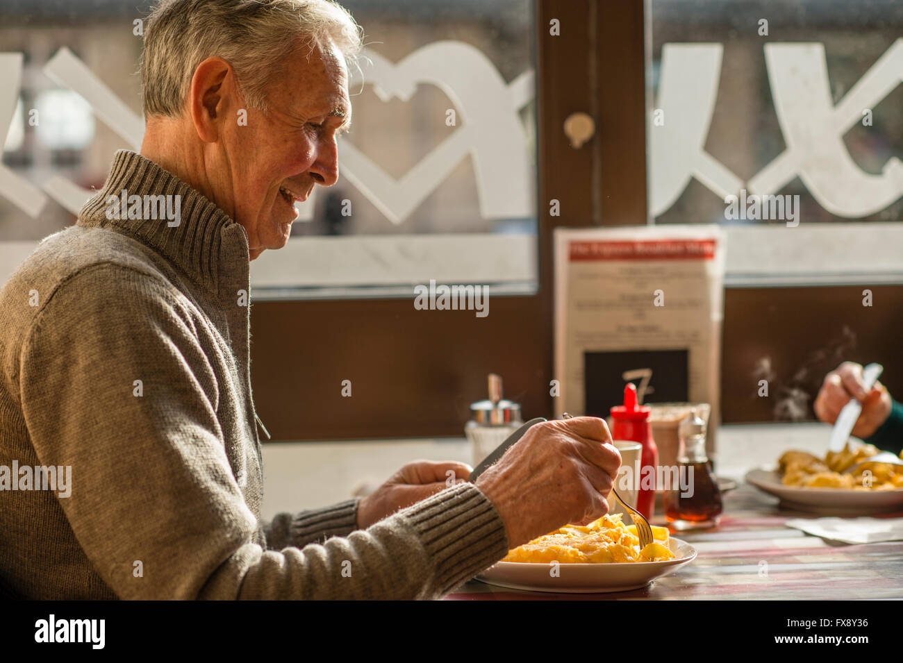 A man eating his dinner of  freshly cooked  fish and chips  in the Express Cafe , a small independently owned local - Stock Image