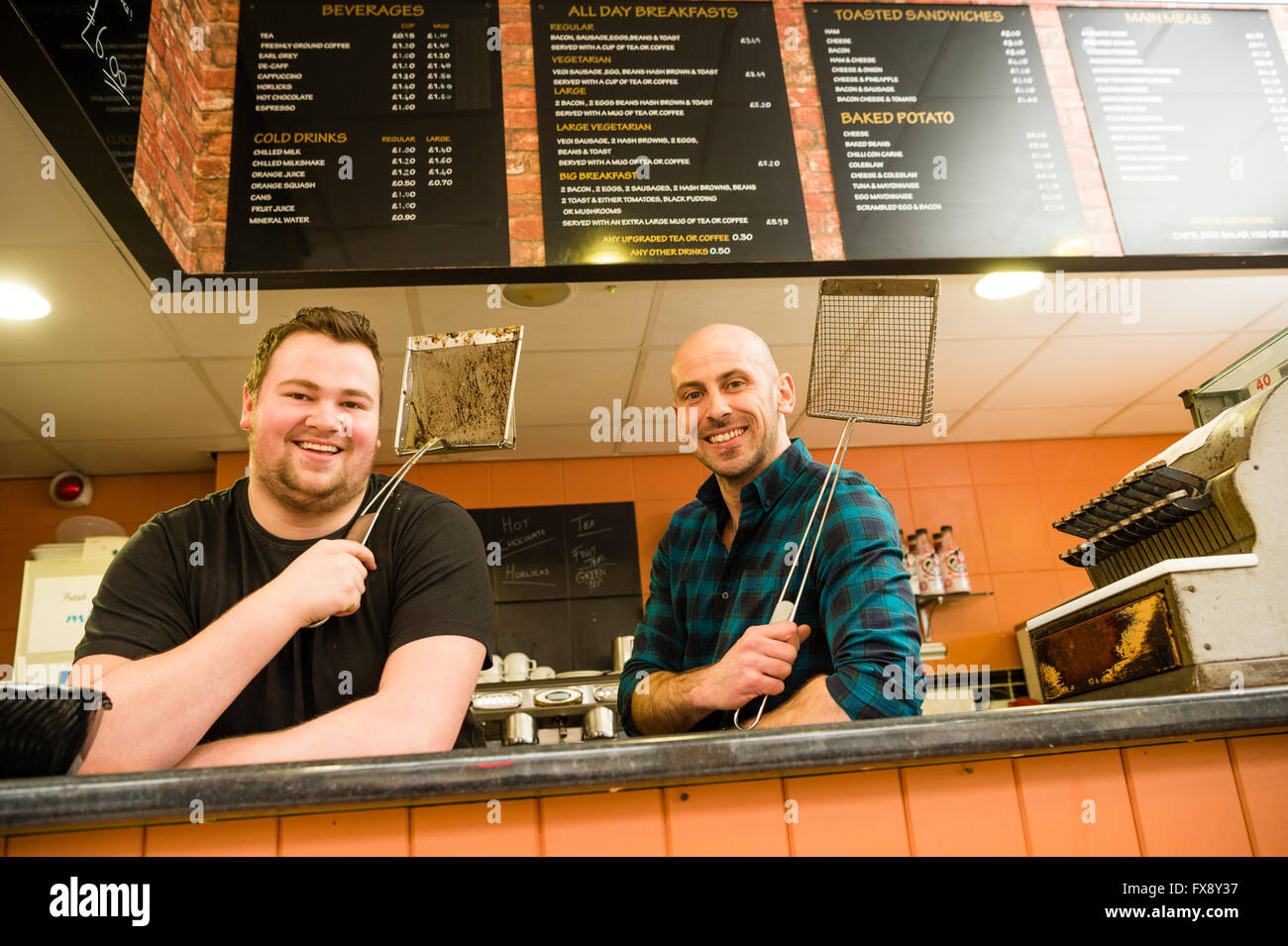 Two men working behind the service counter of the Express Cafe , a small family-owned independent and fish and chip - Stock Image