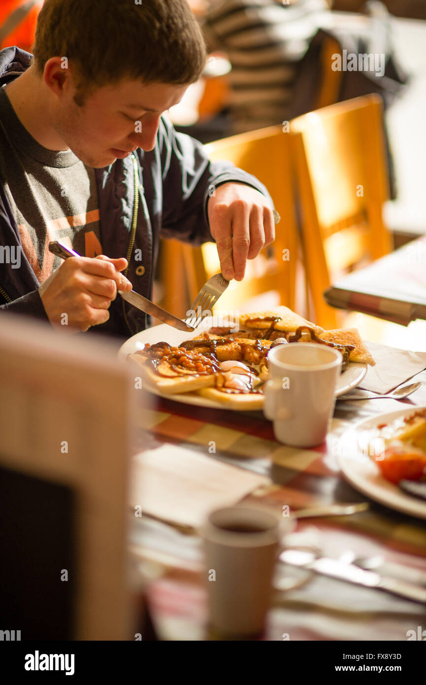 A young man eating a full english breakfast  in the Express Cafe , a small independently owned local fish and chip - Stock Image