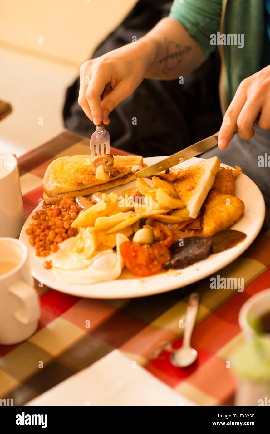 A young man eating a full english breakfast - eggs, sausage, beans, black pudding, chips, tomato, toast,  -  in - Stock Image