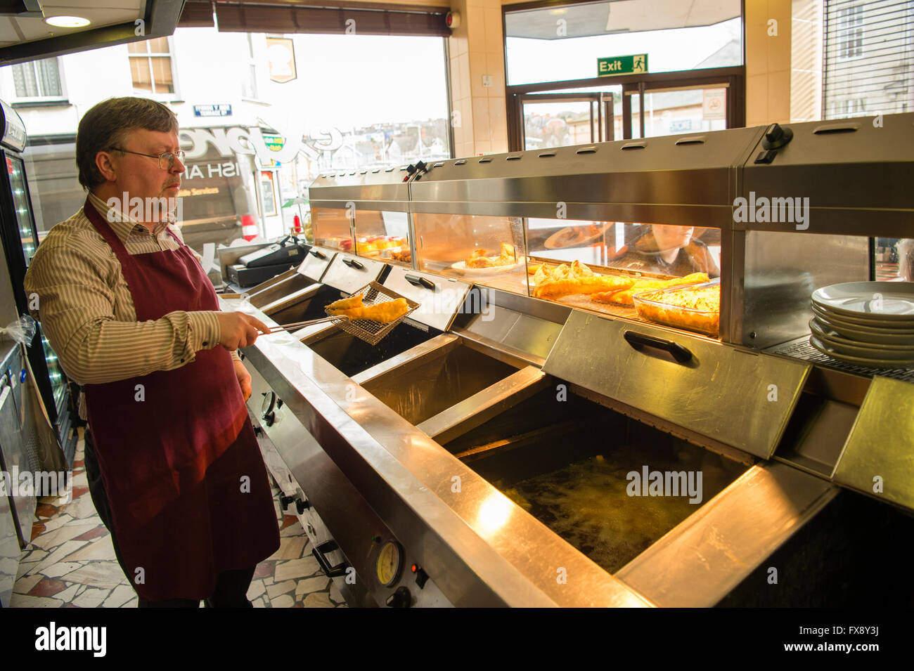 A man working preparing freshly fried food  in the Express Cafe , a small independently owned local fish and chip - Stock Image