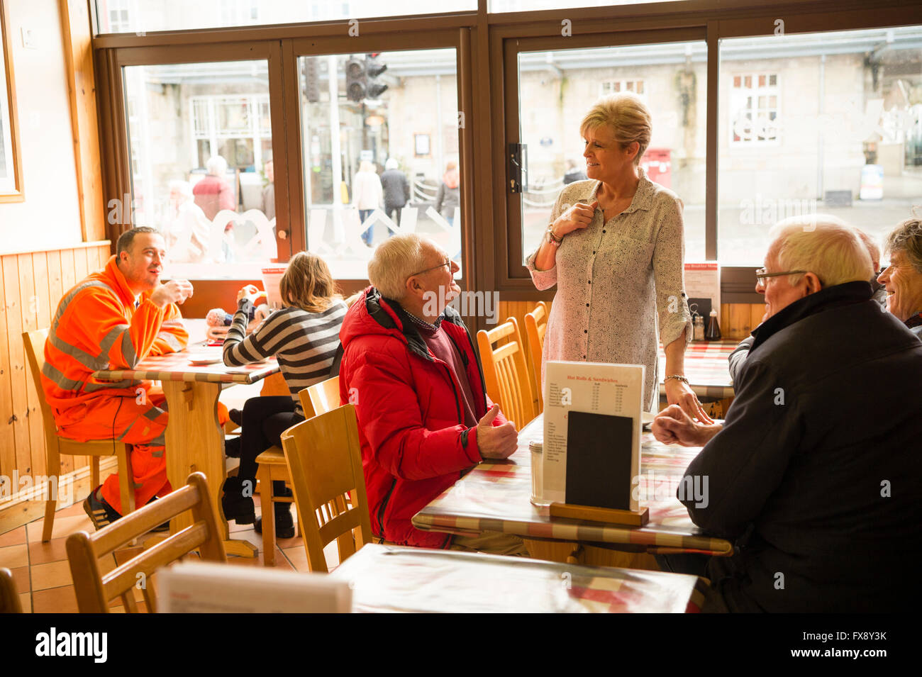 Men talking to the waitress  in the Express Cafe , a small independently owned local fish and chip shop.Aberystwyth - Stock Image