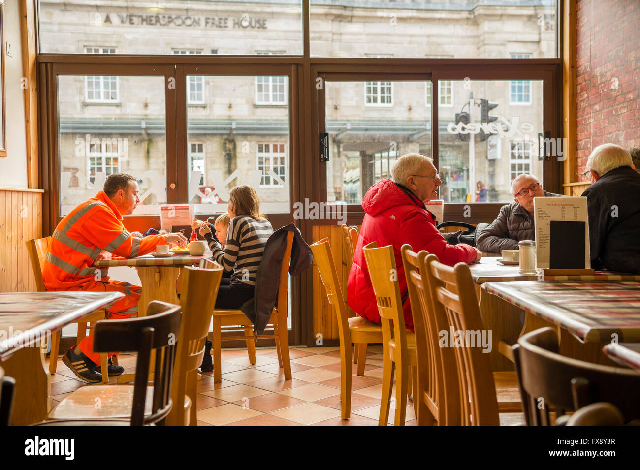People sitting at tables in the Express Cafe , a small independently owned local fish and chip shop.Aberystwyth - Stock Image