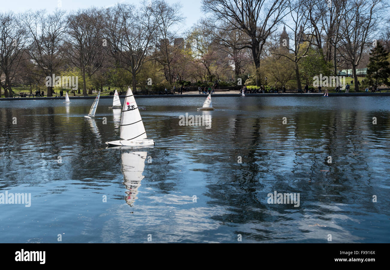 Motorised and wind driven miniature model sailboats on the Conservatory Water in Central Park, New York, in Spring - Stock Image