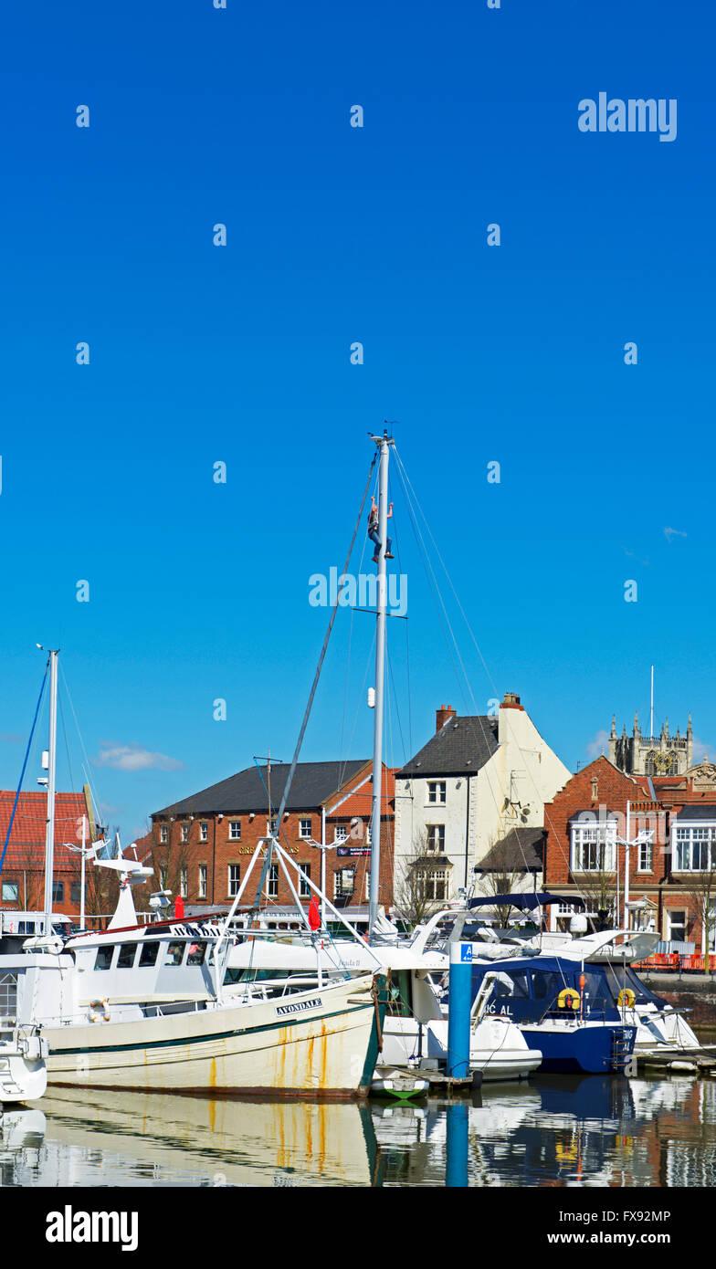 Man climbing mast of yacht moored in the marina, Kingston upon Hull, Humberside, East Yorkshire, England UK - Stock Image