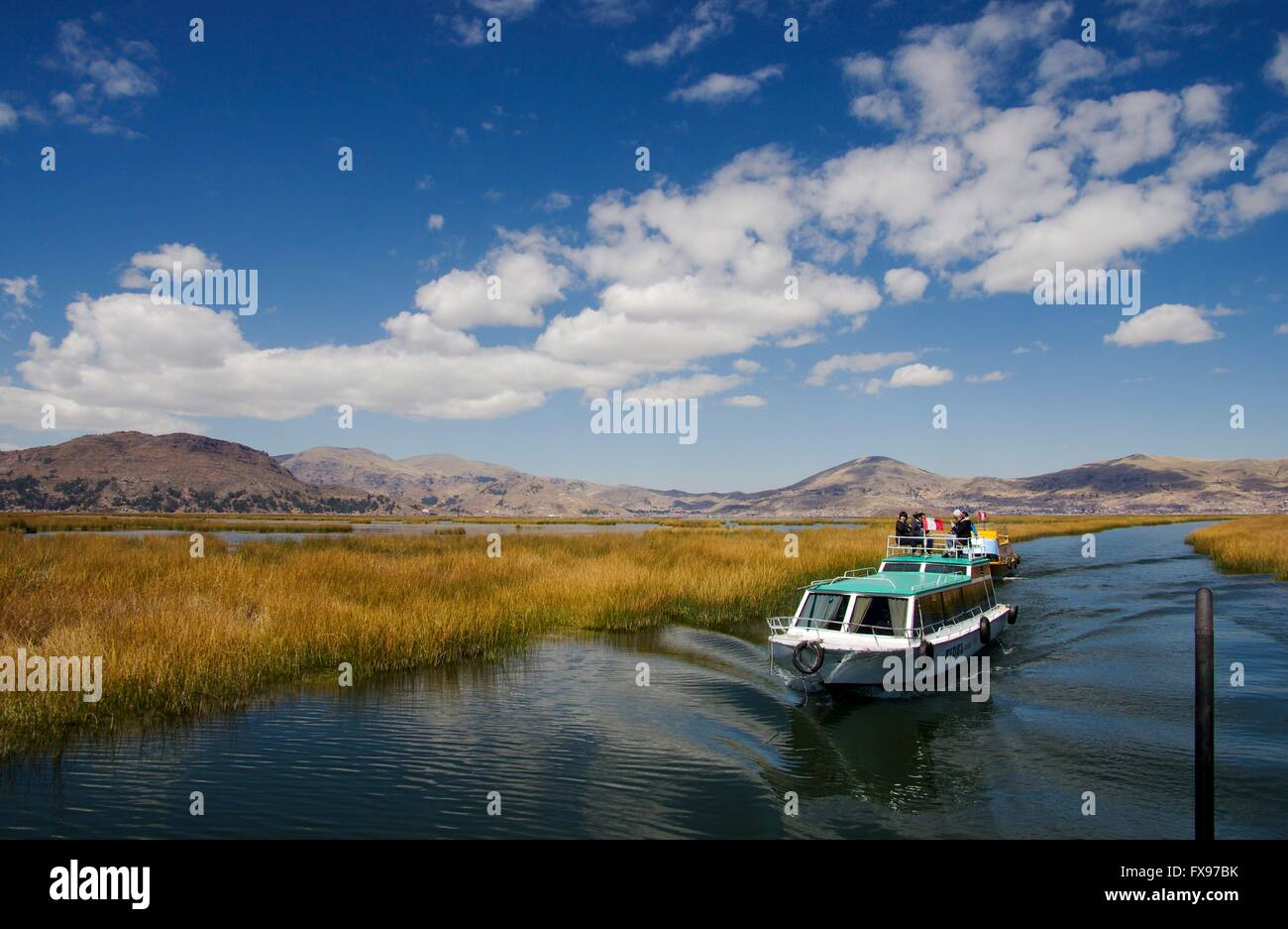 A motor boat on Lake Titicaca takes tourists from Puno's harbour to the reed islands of the Uros people. Picture - Stock Image