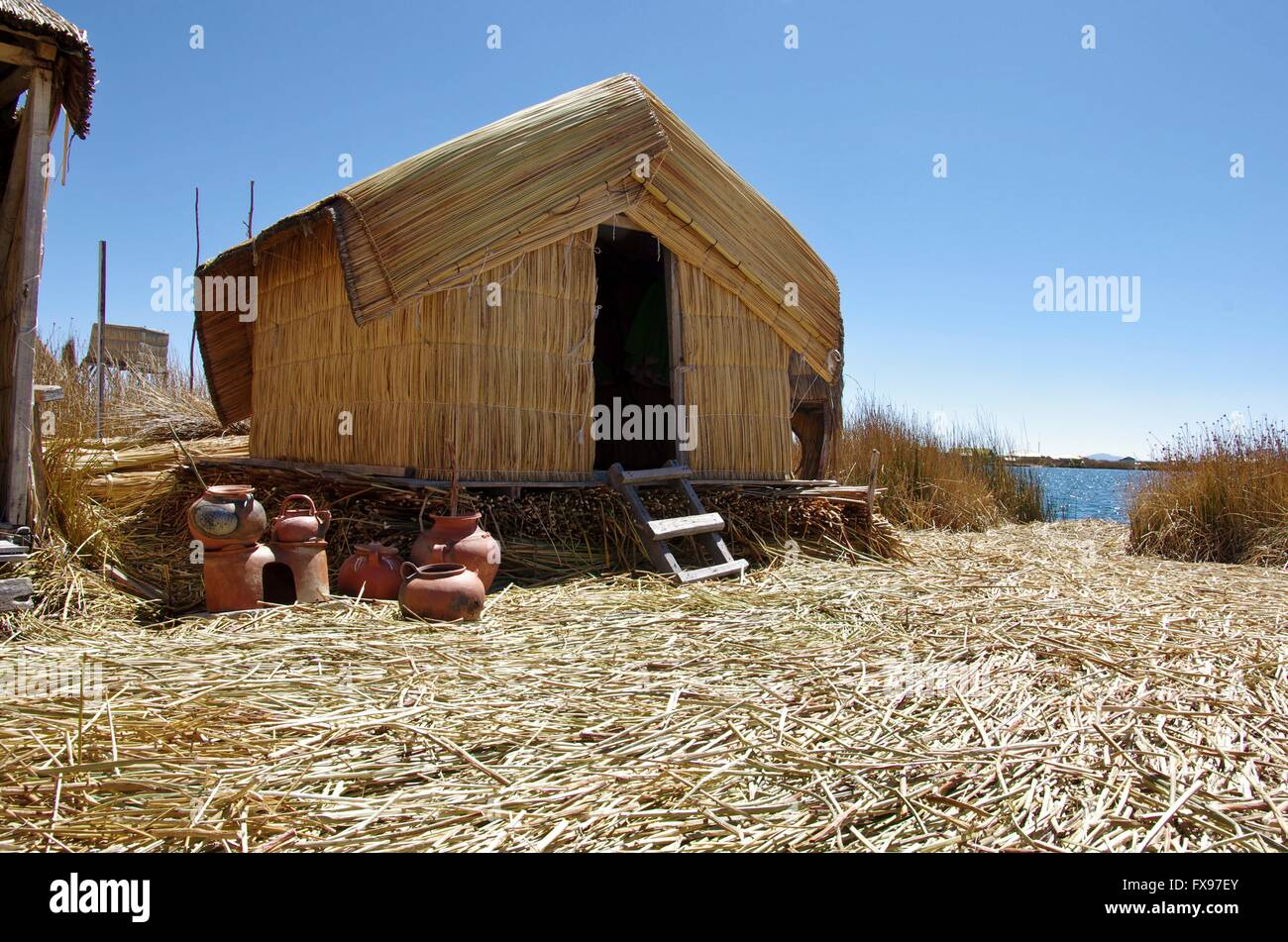 Reed hut/s on a reed island of the Peruvian Uros people, living five kilometers away from Puno on Lake Titicaca. - Stock Image