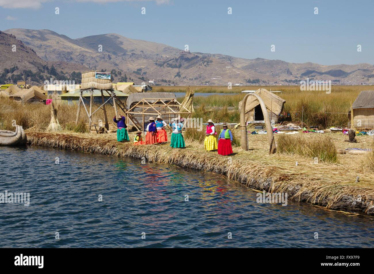 Women of the Uros people welcome tourists on their reed island in Lake Titicaca. Picture taken 2015-08-31. - Stock Image