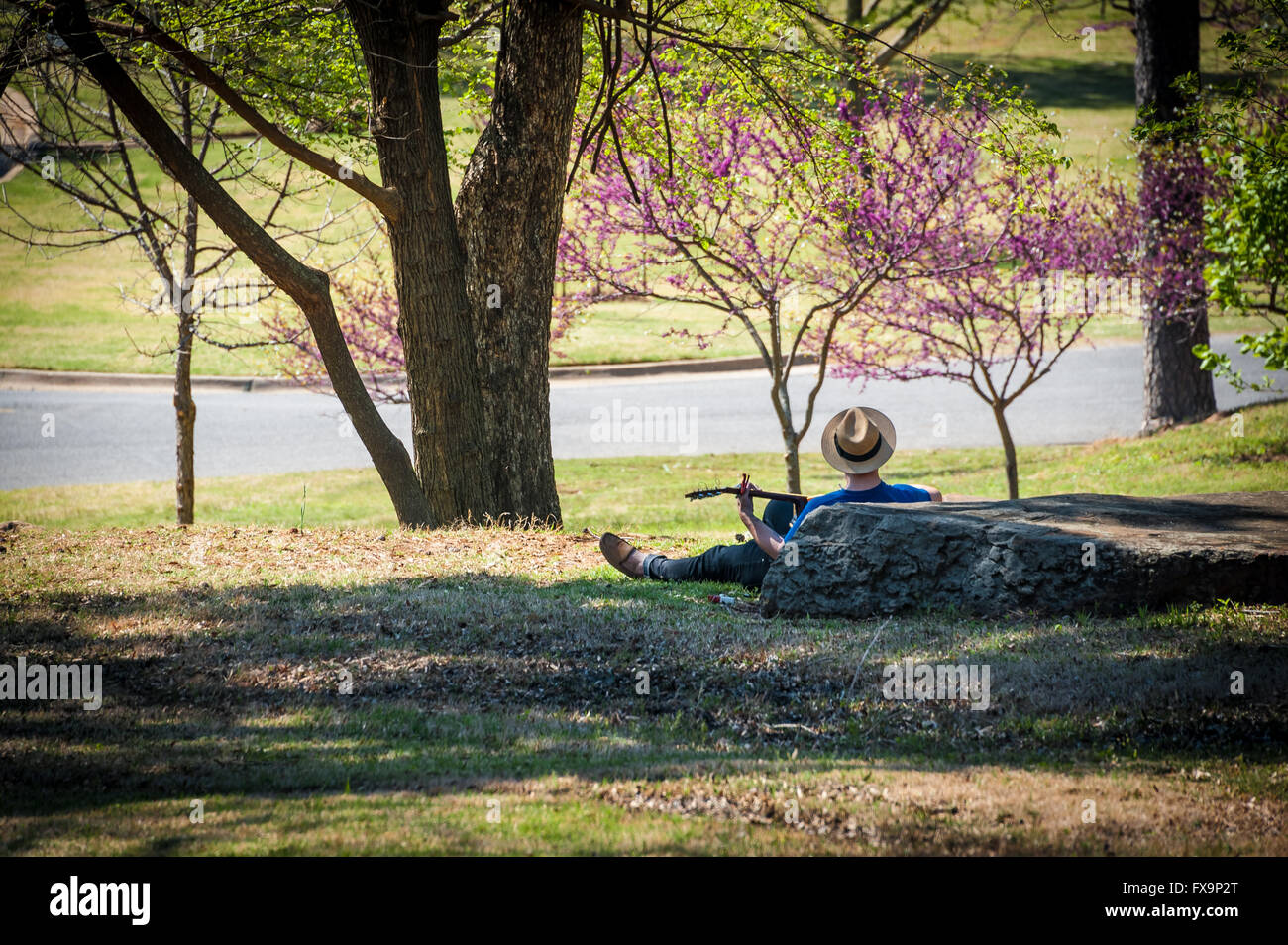 Guitar player enjoying a relaxing springtime afternoon at Honor Heights Park in Muskogee, Oklahoma, USA. Stock Photo