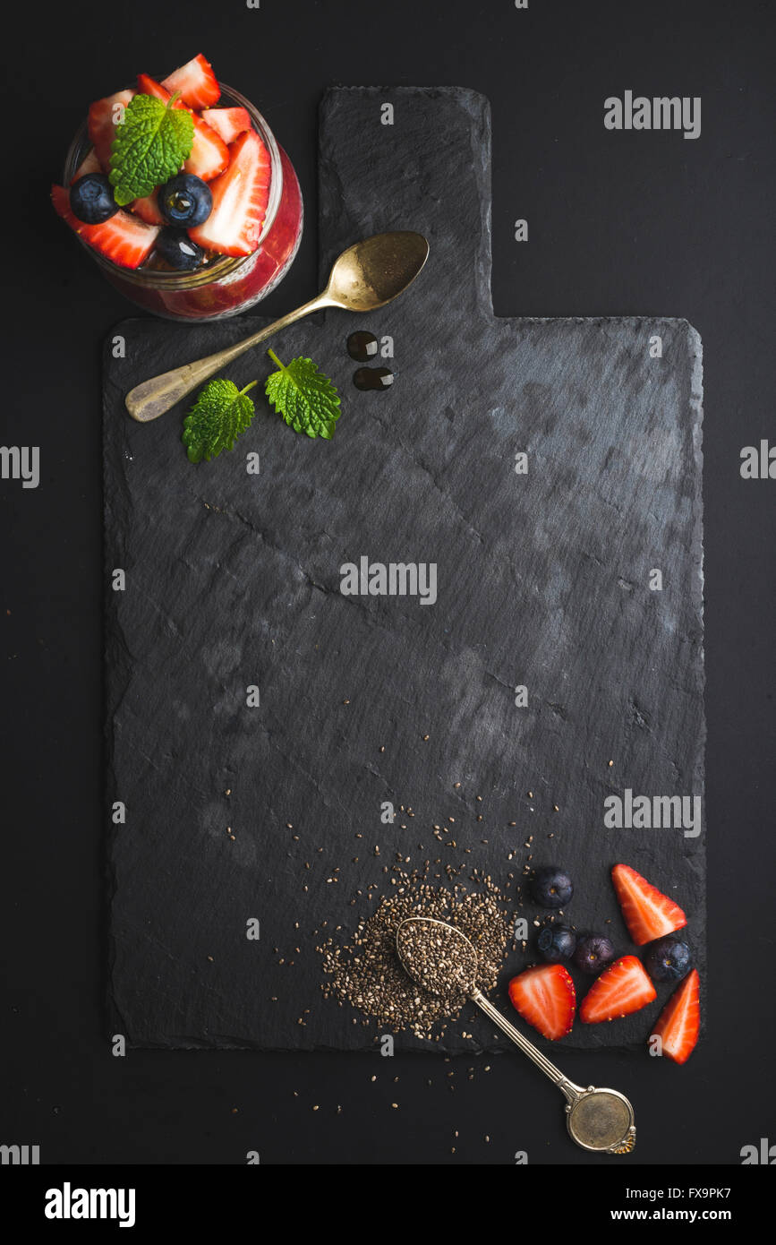 Healthy breakfast food frame. Chia pudding with fresh berries and mint on black slate stone board over dark background. - Stock Image