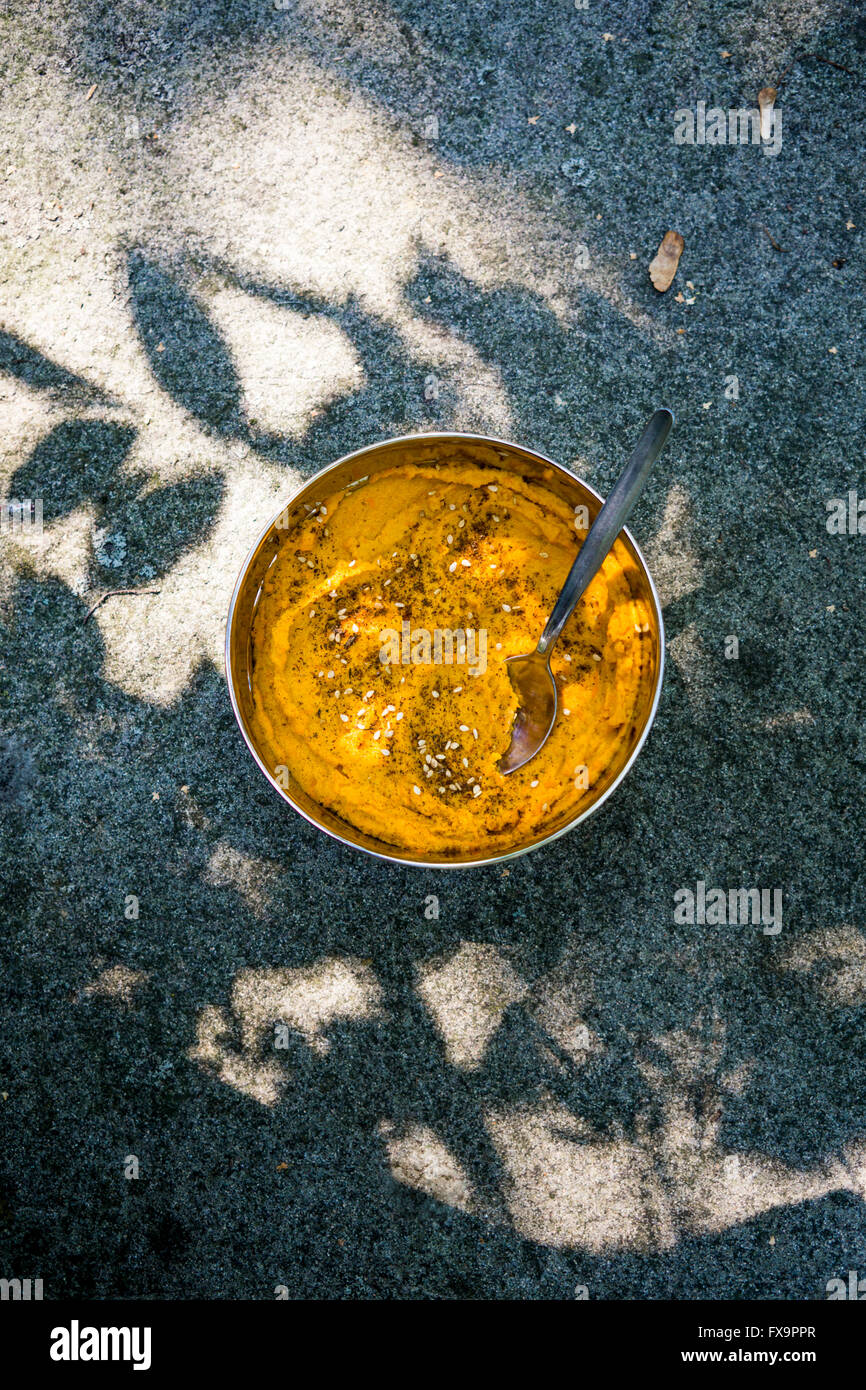 Carrot hummus in steel lunch box with light and shadow playing on the wall. Top view - Stock Image