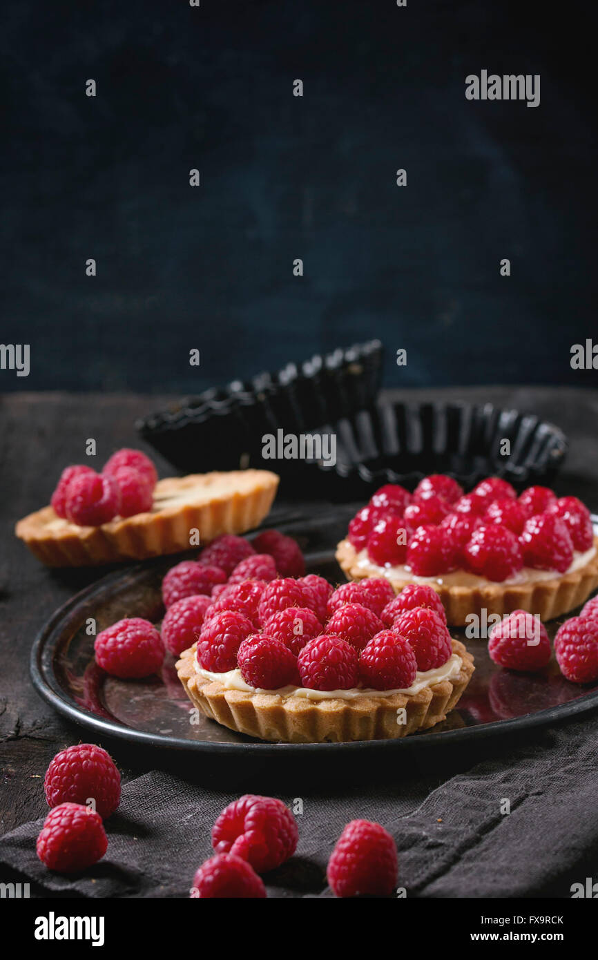 Unfinished and ready to eat tartlets with custard and fresh ripe raspberries, served on vintage metal tray with - Stock Image