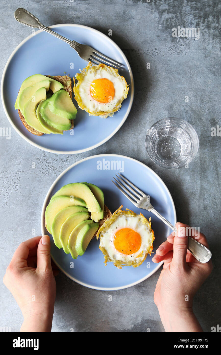 Baked eggs in potato nests with avocado toast - Stock Image