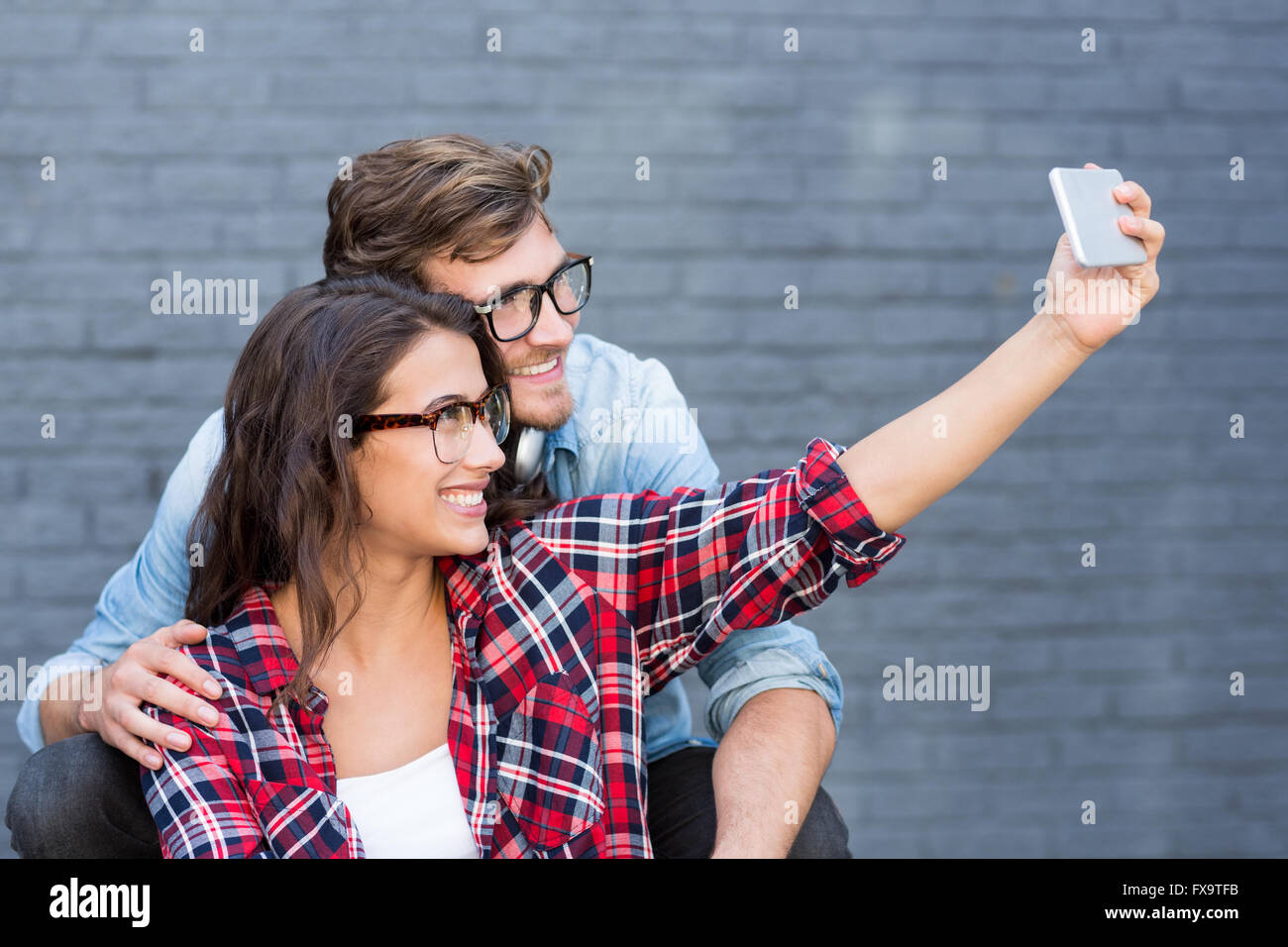 Young couple in spectacles taking a selfie - Stock Image