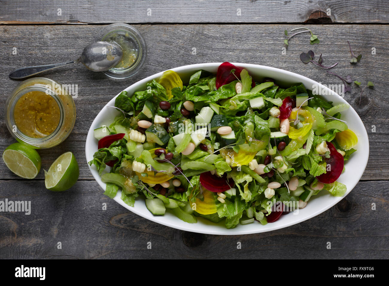 White ceramic bowl full of fresh mixed lettuce salad with healthy toppings, shot areal view with vinaigrette and Stock Photo