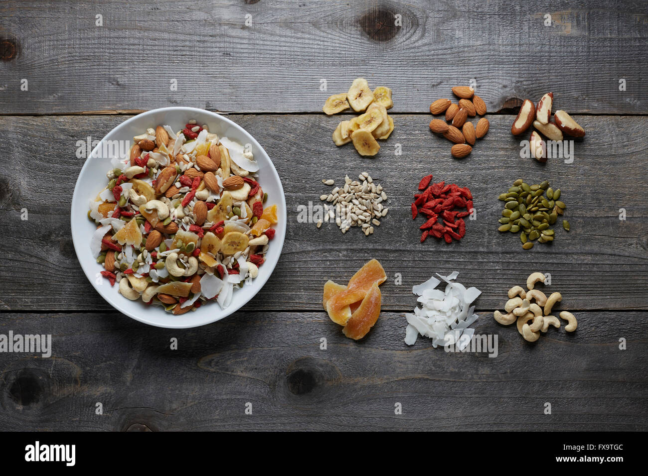 White ceramic bowl full with a healthy trail mix of dried fruits, nuts and seeds. Shot areal view with ingredients Stock Photo