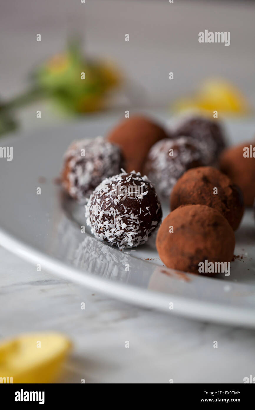 Vegan Chocolate almond date balls on a white plate - Stock Image