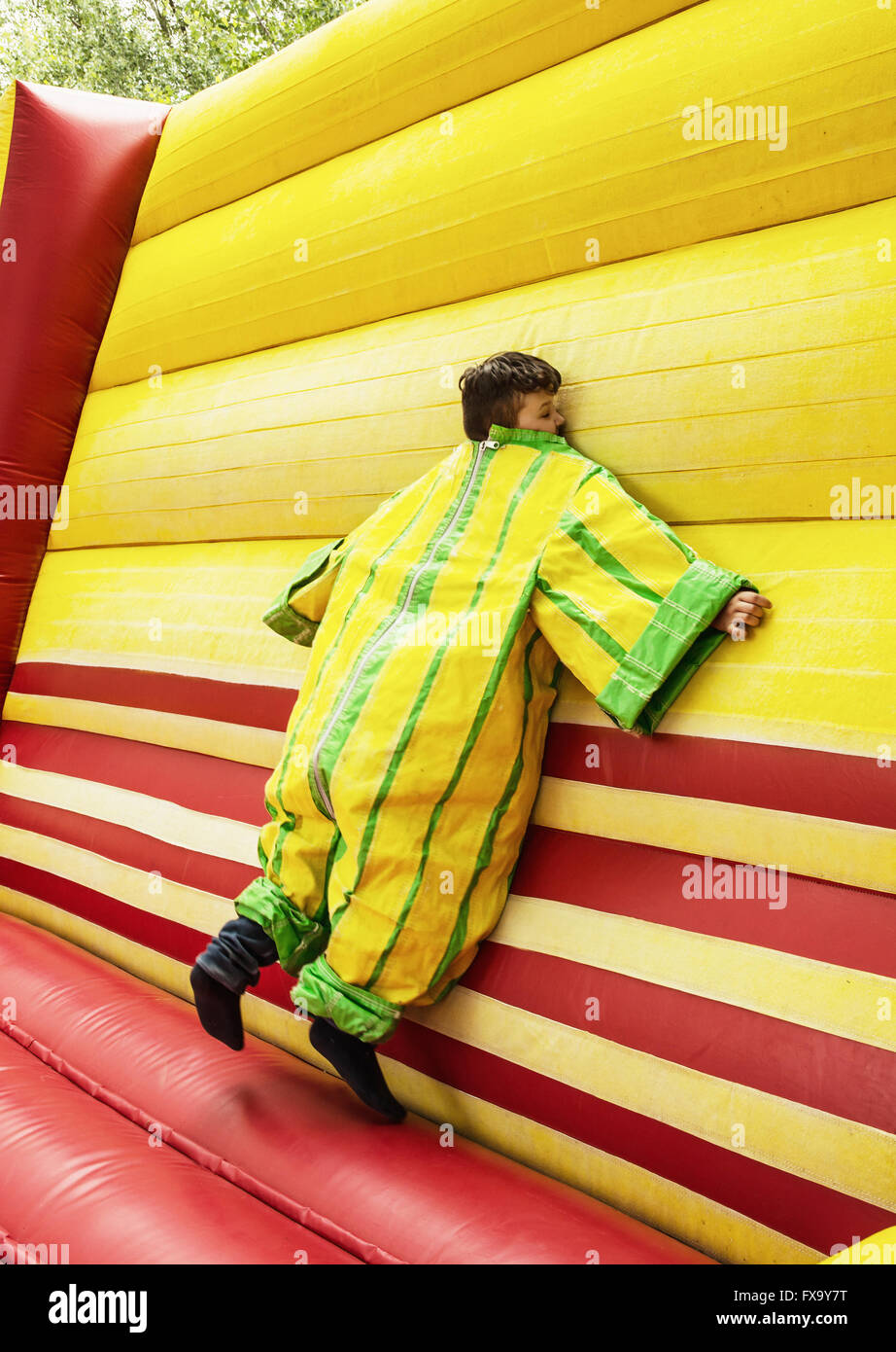 The boy in colorful plastic dress in the bouncy castle. Leisure activity. - Stock Image