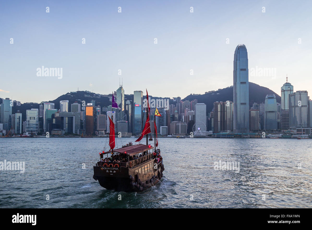 Tourist junk at the Victoria Harbour and Hong Kong Island's skyline in Hong Kong, China. - Stock Image