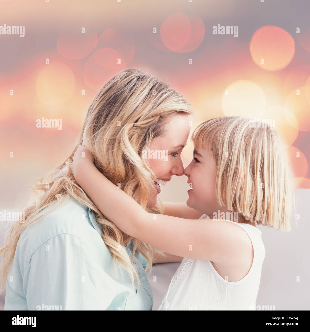 Composite image of mother and daughter rubbing noses on sofa - Stock Image