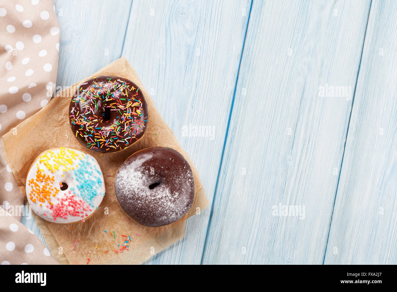 Donuts with colorful decor on wooden table. Top view with copy space - Stock Image