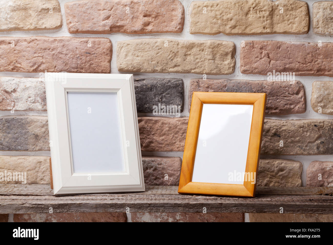 Blank photo frames on shelf in front of brick wall - Stock Image