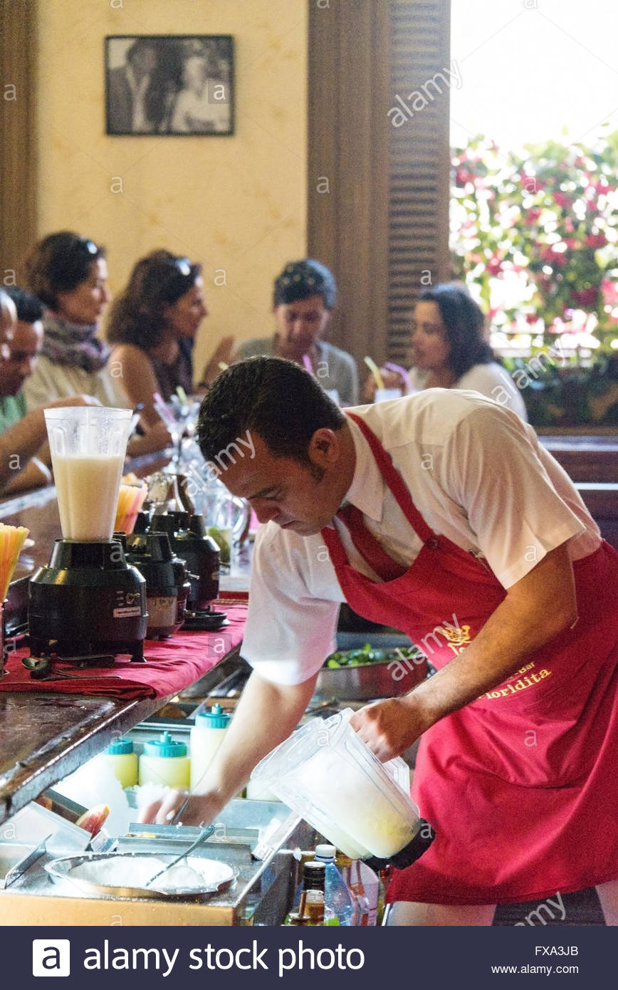 Bartender tending tourists behind the bar counter. Wearing a red apron. - Stock Image